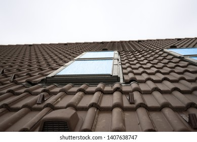 Skylight on ceramic tiles house roof. Skylights, Roof Windows and Sun Tunnels. Natural photo.
