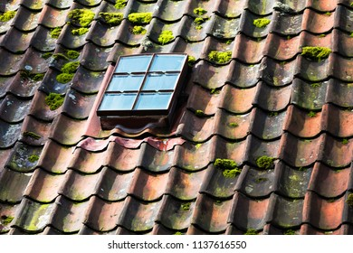 skylight on old ceramic tiles house roof.