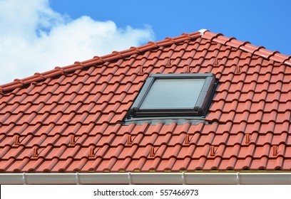 Skylight on red ceramic roof tiles. Modern Attic Roof Skylight. Attic Skylights Home Design. Roofing Construction. Clay Roof Tiles, Clay Roofing. Tile roof.
