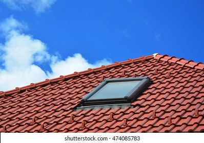 Skylight on red ceramic tiles house roof. Skylights, Roof Windows and Sun Tunnels.