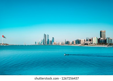 Skyline of Abu Dhabi waterfront with fishing boat crossing the scene. The left corner of the photo shows a huge arab emirates flag.
