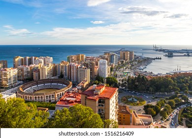 Skyline aerial view of Malaga city, Andalusia, Spain. Plaza de Toros de Malagueta bullring on the left. Autumn sunny evening