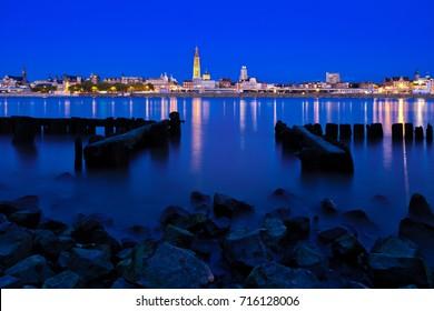 Skyline Antwerp, low water. The lights of Antwerp by night. Reflection of the lights in the Scheldt. Proud our lady cathedral in the skyline.