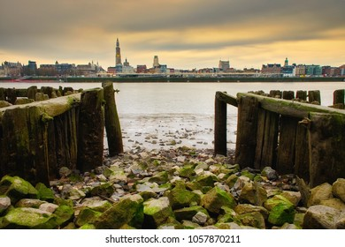 Skyline of Antwerp. The river Scheldt offers a beautiful scene of the city. Rocks in the foreground and the cathedral in the back.
