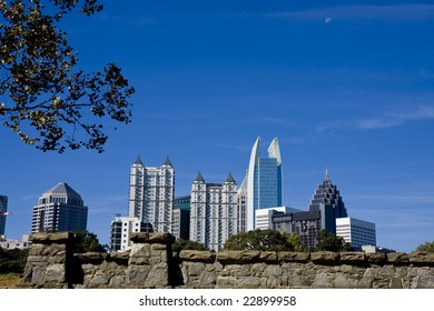 The skyline of Atlanta shot over an old granite stone wall on a sunny day
