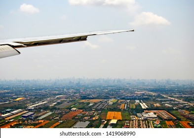 The skyline of Bangkok, far away from the background, seen from an airplane about to land at Suvarnabhumi International Airport.