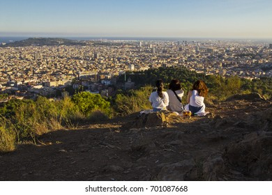 Skyline of Barcelona. 3 girls picnic on a top of a hill city views.