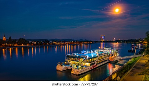 Skyline of Bonn, Germany. Beautiful night shot of great german city. Water reflections of night lights, trees, landmark buildings and big liner ship near the quay