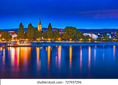 Skyline of Bonn, Germany. Beautiful night shot of great german city. Panorama with boat and historic architecture reflected in the water.