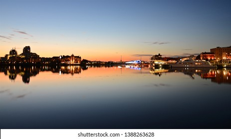 skyline with the bright evening lights of Victoria City and sunset rays. lights form a mirror image on the water of the bay, British Columbia, Canada, Vancouver island