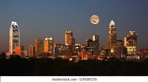 Skyline of Charlotte, NC, at sunset with a full moon overhead.