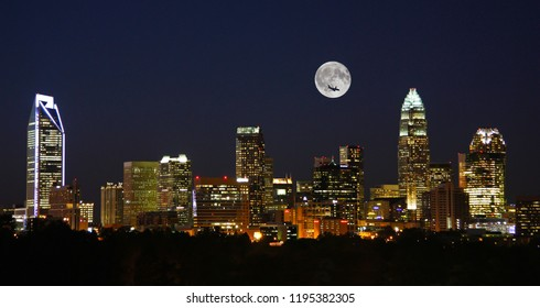 The skyline of Charlotte, North Carolina, at night with full moon overhead.