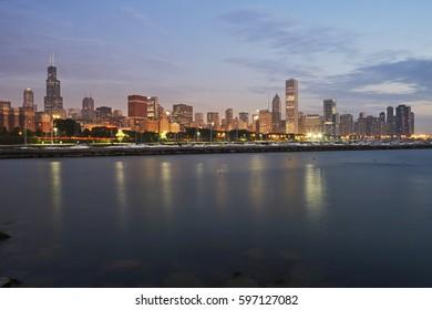 Skyline of Chicago over lake Michigan illuminated at sunrise