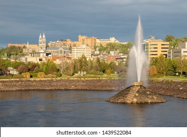 Skyline of Chicoutimi on the Saguenay River with fountain spouting water in the evening light