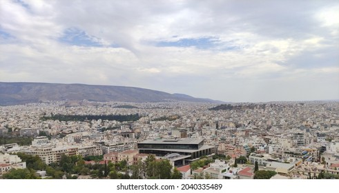 The skyline of the city of Athens, as seen from the Akropolis, during a cloudy, summer day. The Akropolis museum is in the middle.