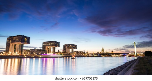Skyline of Cologne, Germany with Crane Houses and Cathedral after sunset.