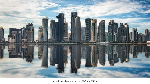 The skyline of Doha, Qatar, on a sunny day with reflections in the water