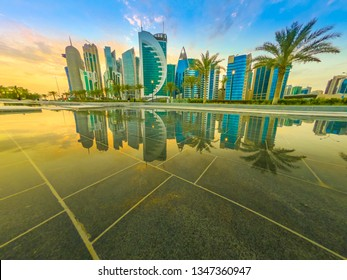 Skyline of Doha, Qatar at sunset sky. Scenic cityscape of West Bay skyline miroring in the water of downtown park. Middle East, Arabian Peninsula in Persian Gulf. Copy space.