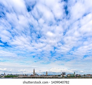 Skyline of downtown Antwerp (Antwerpen), Belgium, as seen from the opposite side of the River Scheldt, under a blue sky with clouds
