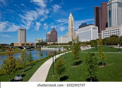The skyline of downtown Columbus, Ohio along the Scioto River is crisp and clear.  Wispy clouds in the sky add drama to the cityscape.