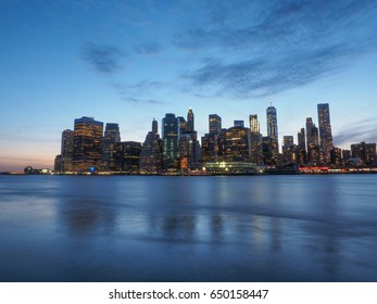 Skyline of Downtown New York and Manhattan from Brooklyn Bridge Park after sunset in New York City, USA