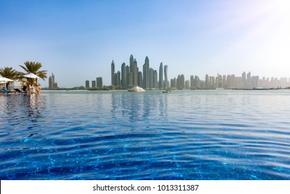 The skyline of the Dubai Marina with a pool in front of it