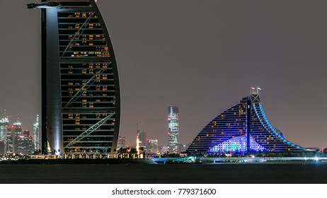 Skyline of Dubai at night timelapse with Burj al Arab in foreground in Dubai, United Arab Emirates. View from palm jumeirah