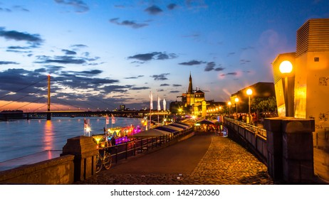 Skyline of Dusseldorf, the capital of the German federal state of North Rhine-Westphalia, in a beautiful sunset with the Rhine on the left and the Pegeluhr and St. Lambertus Basilika on the right.
