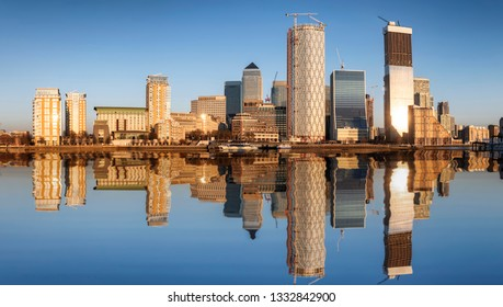 The skyline of the financial district Canary Wharf in London, UK, with the modern skyscrapers and constructions sites during sunset time