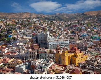 Skyline of Guanajuato City in Mexico with colorful buildings and Basilica of Our Lady against cloudy blue sky.