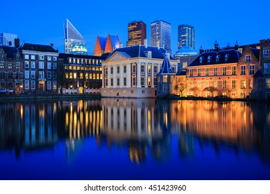 Skyline of The Hague with the modern office buildings behind the Mauritshuis museum and the Binnenhof parliament building next to Hofvijver lake in the Netherlands at dusk during the blue hour.
