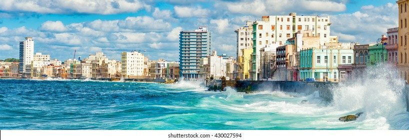 The skyline of Havana with a view of sea waves crashing against the Malecon wall