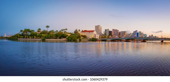 The skyline of the historic city of Recife in Pernambuco, Brazil by the Capibaribe river at sunset.