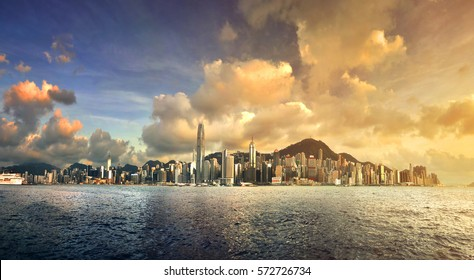 Skyline of Hong Kong with at sunset with a dramatic sky over the Victoria harbor.