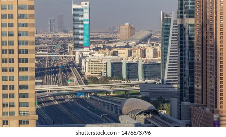 Skyline internet city with crossing Sheikh Zayed Road aerial timelapse before sunset. Skyscrapers with traffic on a highway and metro line in Dubai