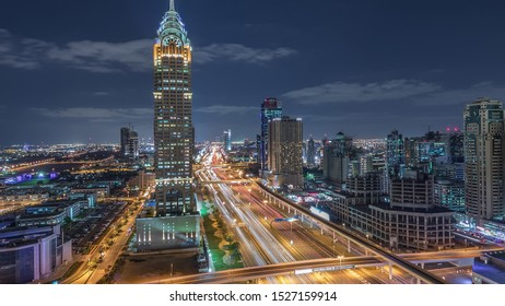 Skyline internet city with crossing Sheikh Zayed Road aerial night timelapse. Illuminated skyscrapers with traffic on a highway and metro line in Dubai