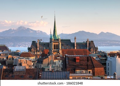 Skyline of Lausanne, Switzerland as seen from the Cathedral hill at sunset zoomed-in on the tower of St-Francois Church. Lake Leman (Lake Geneva) and the French Alps provide a beautiful background.