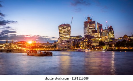 The skyline of London in the UK by the Thames river at night.