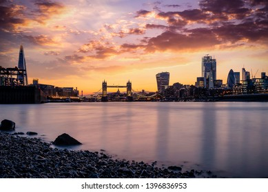 The skyline of London, UK, during sunset time seen from the Thames river to the Tower Bridge and City
