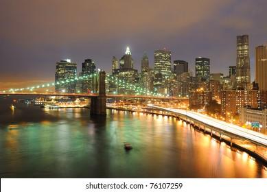 Skyline of Manhattan and Brooklyn Bridge in New York City at night.