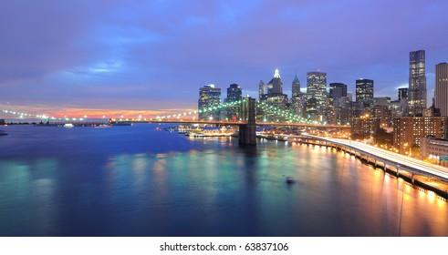 Skyline of Manhattan and Brooklyn Bridge with setting sun behind it.