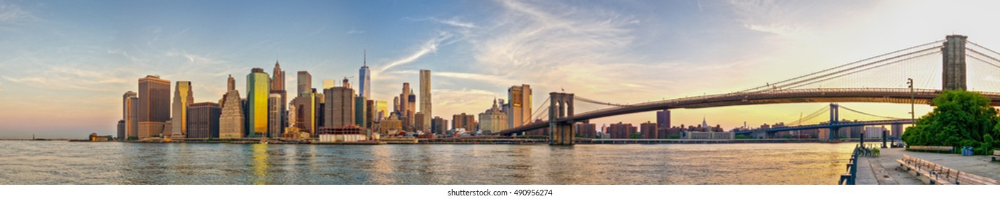 Skyline of Manhattan during sunrise on a beautiful summer morning. Includes Statue of Liberty. Panorama.