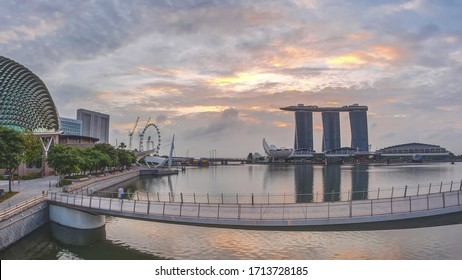 Skyline in Marina Bay with Esplanade Theaters on the Bay and Esplanade footbridge early morning view in Singapore during sunrise. Skyscrapers reflected in water