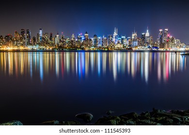 Skyline of the Midtown Manhattan at night with vivid reflections of city lights in the Hudson River as seen from Weehawken, NJ.