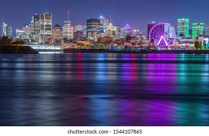 Skyline of Montreal, Quebec, Canada at night with reflections of skyscrapers lights on the Saint Lawrence River giving off a palette of colors on the water surface. A purple ferris wheel is present.