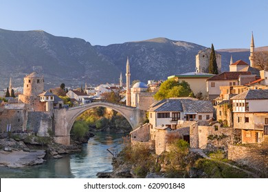 Skyline of Mostar with the Mostar Bridge, houses and minarets, at the sunset in Bosnia and Herzegovina.