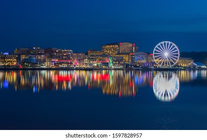 Skyline of the National Harbor illuminated waterfront, a tourist attraction on the banks of the historic Potomac River in Prince Georges County Maryland.