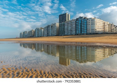 The skyline of Ostend City with its waterfront promenade reflected in the North Sea with sand patterns at sunset, West Flanders, Belgium.