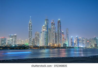 A skyline panoramic view of Dubai Marina showing the Marina and JBR with glittering lights and tallest skyscrapers during a clear evening with Blue sky.