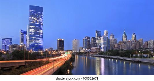The skyline of Philadelphia of dusk. Schuylkill expressway traffic runs parallel to Schuylkill River.
